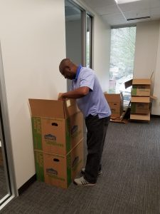 Aaron Holly unpacks boxes in the new Raleigh office